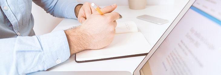 Person schreibt etwas in Notizbuch für den perfekten Titel der Stellenanzeige