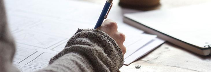 Bewerber schreibt mit Stift auf einem Papier ein Bewerbungsschreiben