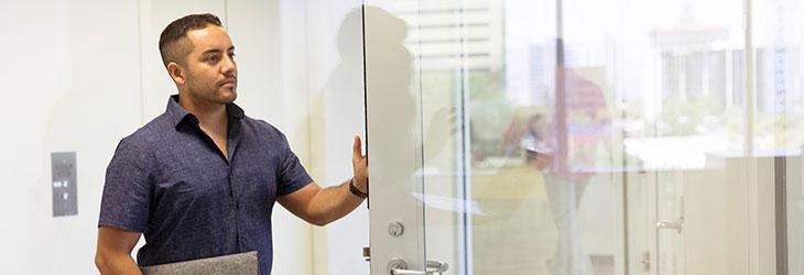 Mann geht durch Tür am ersten Arbeitstag