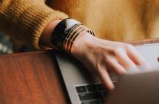 Frau ist mit Laptop auf Jobsuche beim Berufseinstieg