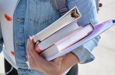 Person hat Mappen und Bücher auf dem Arm